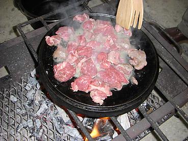 ダッチオーブンのふたを裏返して牛肉を炒める